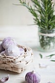 Field garlic in a basket with sprigs of rosemary in a glass in the background