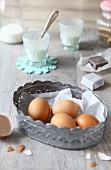 Four brown eggs in a metal basket on a wooden surface with various baking ingredients