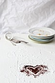A cocoa powder heart, a stack of plates, a sieve and a cake slice on a floured work surface