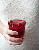 A woman holding a glass of cranberry juice