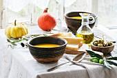 Lunch mit Kürbissuppe und grünen Oliven, serviert auf altem Holztisch beim Fenster