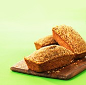 Three loaves of banana bread on a wooden board