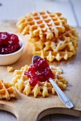 Fresh waffles on a wooden board, one with a teaspoon of strawberry jam