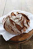 A rustic loaf of country bread on a wooden board with a white cloth