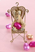 A plush Easter Bunny and chocolate eggs wrapped in foil on a miniature chair