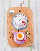 A boiled egg in an egg cup on a chopping board