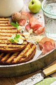 Grilled bread with butter, Parmesan, ham crisps, walnuts, apple and a glass of water