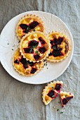 Mini quiches with beetroot and thyme on a white plate