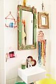 Abgeblätterter, mit Schmuck behängter Spiegelrahmen und Drahtkörbchen mit Perlenketten und Kosmetikutensilien über Handwaschbecken