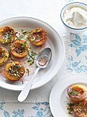 Caramelised nectarine halves with basil and pistachios served with whipped cream