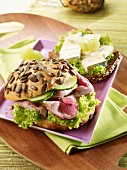 Pumpkin seed rolls with roast beef and protein bread topped with blue cheese