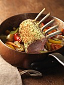 Saddle of lamb on a bed of vegetables in a copper pan