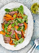 Warm pumpkin salad with lamb, lamb's lettuce and hazelnuts