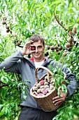 A peach farmer showing his harvest