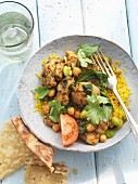 Chicken curry with chickpeas, beans and coriander on a bed of rice