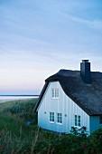 Reetgedecktes Haus in Abenddämmerung in Ahrenshoop an der Ostsee