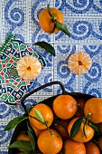 Tangerines with leaves on decoratively patterned tiles