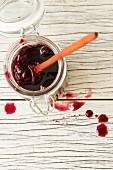 Cherry jam in a jar with a wooden spoon