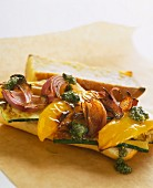 A sandwich with roasted yellow peppers, red onions, garlic and pesto