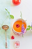 Raspberry and tomato gazpacho garnished with a sprig of lavender
