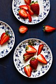 Fresh strawberries, whole and halved, on floral-patterned plates