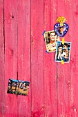 Old Mexican photos on wooden wall painted red