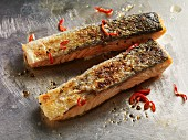 Two crispy grilled salmon fillets with black pepper and chilli strips on a metal surface