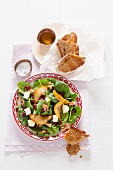 Spinach salad with pomegranate seeds, caramelised pear crisps and Brie