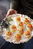 Mini pancakes with smoked salmon and basil on a silver platter