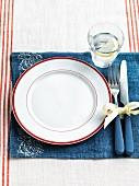 Leerer weißer Teller mit rotem Rand auf blauem Tischset mit Glas Wasser