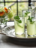 Three glasses of vodka Limoncello garnished with mint on a silver tray