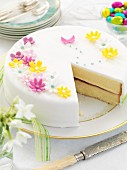 An Easter cake with white icing and sugar flowers