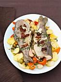 Gebackene Forellen mit Kräutern, Butter und Gemüse auf Teller