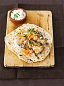 Homemade wheat tortillas with chicken skewers, yoghurt, carrots and onions