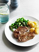 Herb steak with a pea and asparagus medley and potatoes
