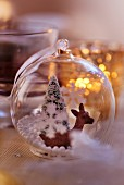 Transparent Christmas tree bauble with deer and Christmas tree figures inside decorating table (close-up)