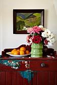 Rosenstrauss und Schale mit Orangen auf bäuerlicher Kommode mit abblätternder Farbe, an Wand Gemälde mit Landschaftsmotiv