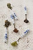 Various types of tea leaves (matcha, Earl Grey, rooibos, sage, jasmine) on spoons