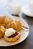 Scones with cream and raspberry jam