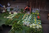 Fresh fruit and vegetables laid out on fresh banana leaves on a market stall in Thailand