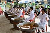 Thailändische Frauen in weissen Kleidern bei der Zubereitung von traditionellem, süssen Reis