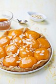 Tarte tatin with peaches, flaked almonds and maple syrup