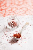 Saffron threads on a spoon and in a jar