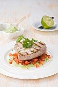 Tuna fish steak on avocado cream and tomatoes