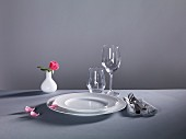 A place setting against a grey background: plates, cutlery, empty glasses and a flower vase