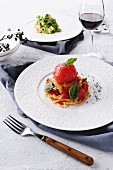 Pasta with tomatoes and basil served with a glass of red wine