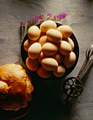A bowl of brown eggs, an old whisk and bread