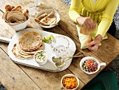 Unleavened bread and various side dishes on a rustic wooden table (India)