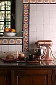 Alte Landhausküche mit Küchenmaschine im Vintage Stil auf rustikalem Unterschrank vor Dekorstreifen mit bunten Musterfliesen