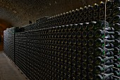 Old wine bottles in metal racks in a vaulted cellar